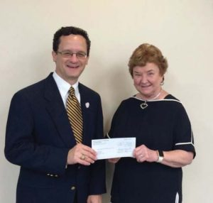 Knowlton presents a check for scholarships to Sr. Kathleen Coughlin, CCVI, vice president for institutional advancement.
