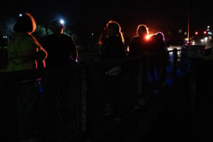 Students and staff gathered for the night's PIT Count. Silhouettes against a dark sky.