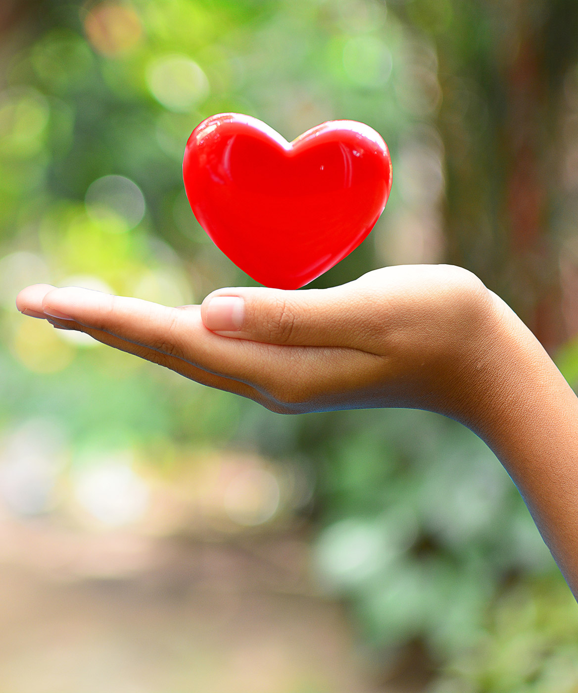 red plastic heart in girl's hand
