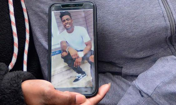 A relative of college football player Dwane Simmons shows his photo after he was shot dead last week.