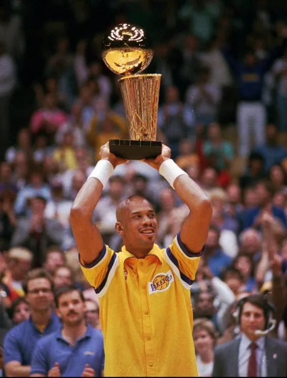 Kareem Abdul-Jabbar holds the Larry O'Brien Trophy during the Lakers' season-opening celebration of their 1987 title on Nov. 6, 1987. LENNOX MCLENNDON, Associated Press
