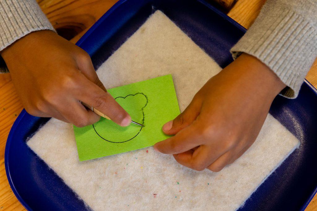 child doing art poking holes in outline