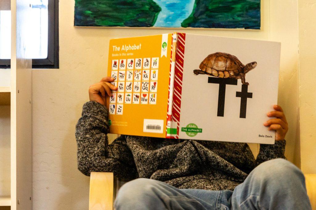 Montessori child reading on a chair