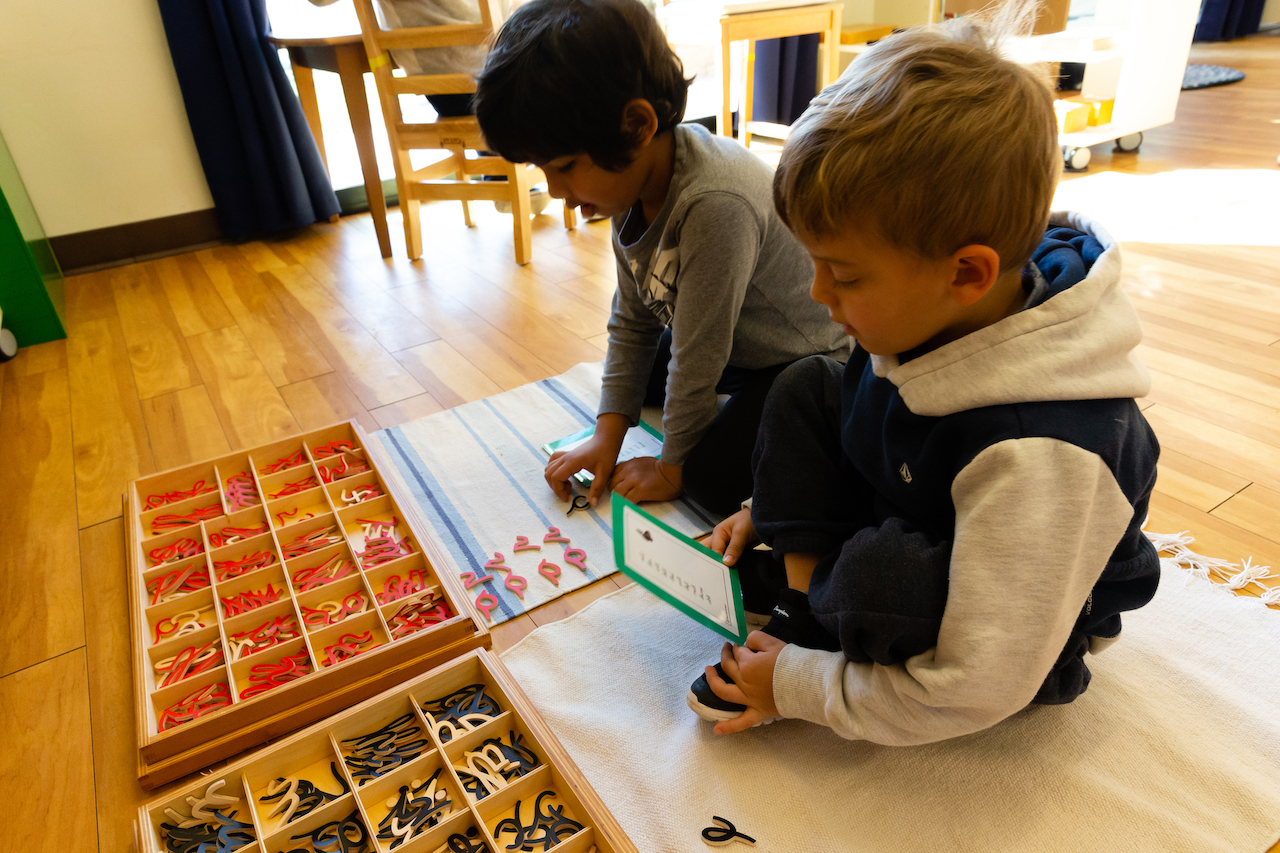 two boys writing using wooden cursive letters in a Montessori Classroom