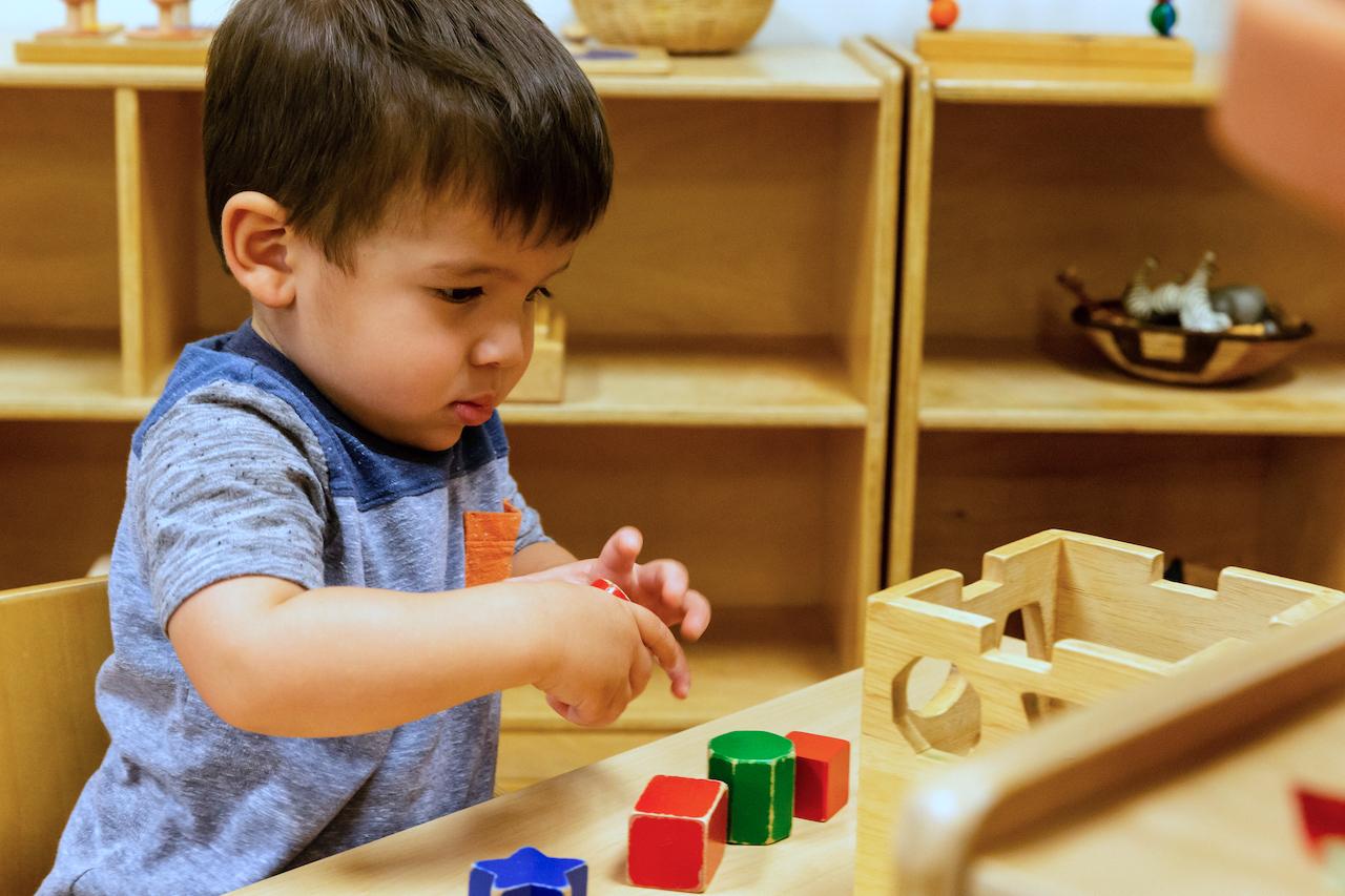 Boy playing with puzzles La Jolla Montessori School