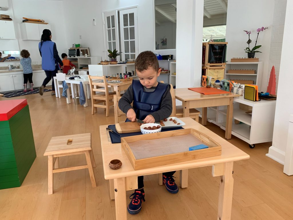 Independent Toddler cutting fruit at La Jolla Montessori school