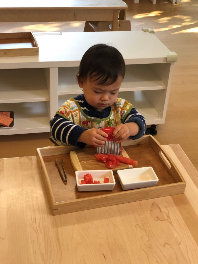 Toddler independently cutting fruit