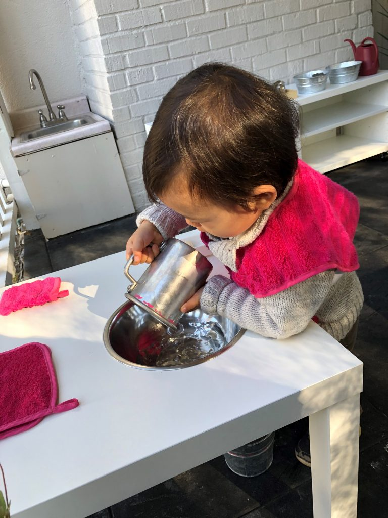 Toddler independently pouring water into sink