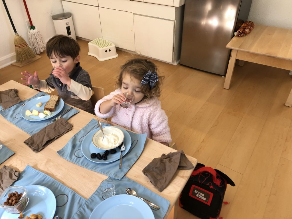Toddlers eating together in a Montessori classroom