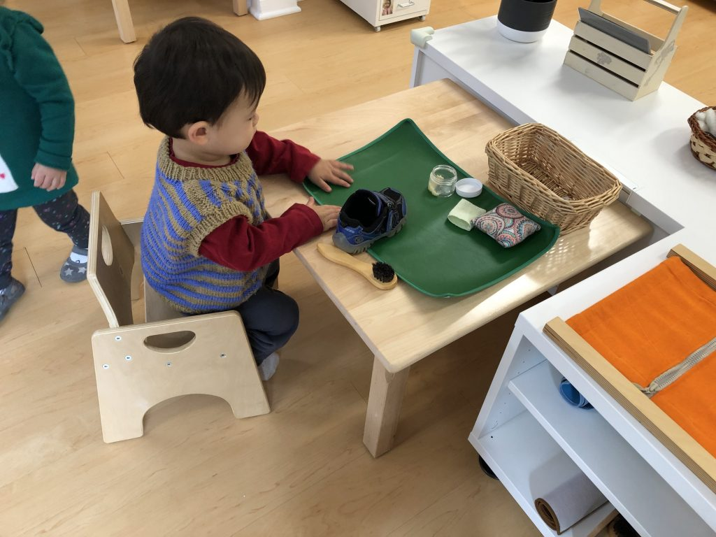Toddler cleaning his shoes independently