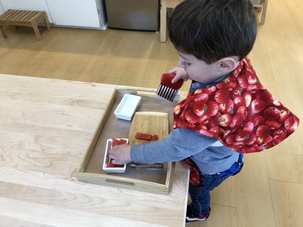 Toddler cutting fruit independently