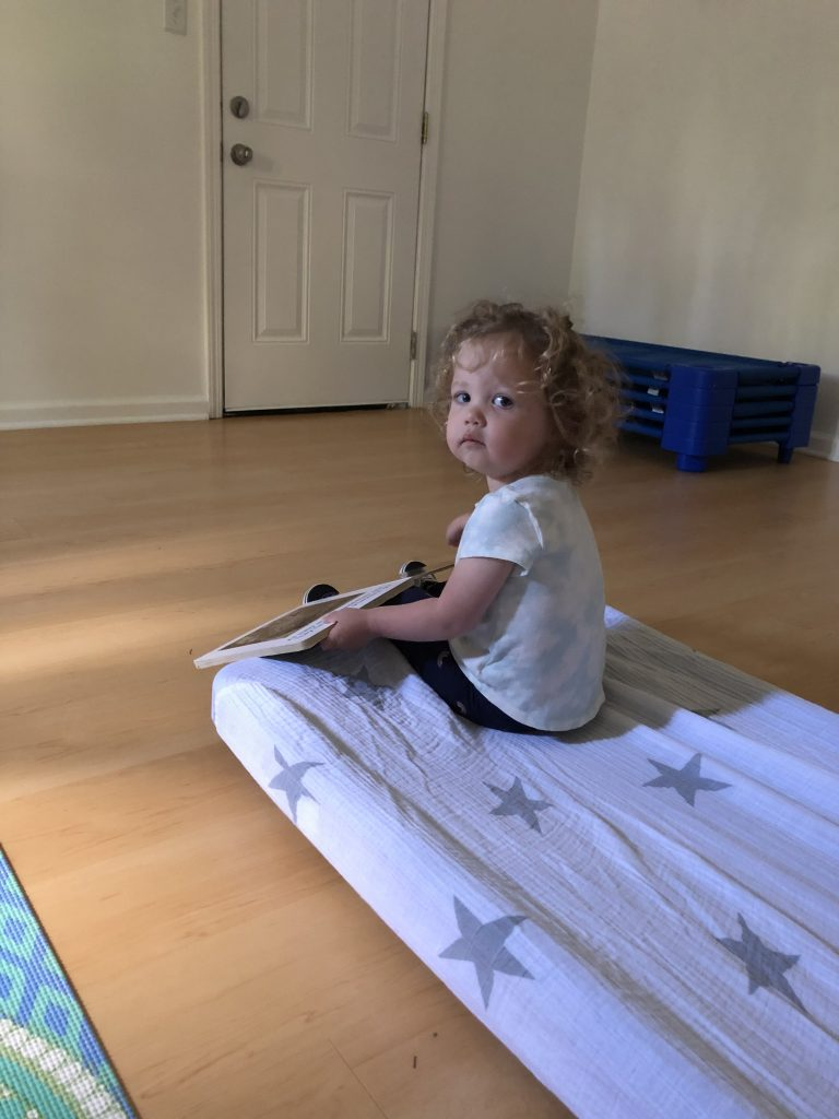 Preschooler ready to read and nap at preschool