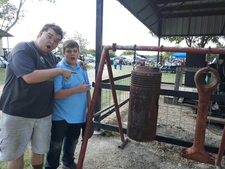 Two of the Riley boys marvel over a giant piston at the Texas Early Days Tractor and Engine Association show in Temple, Texas