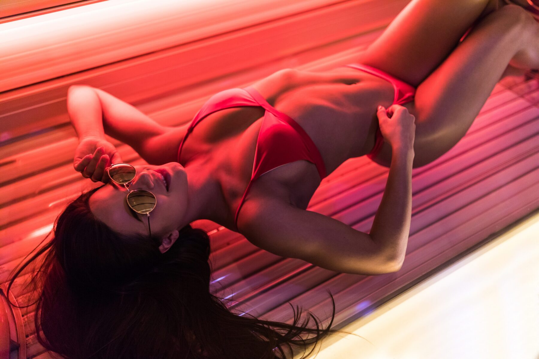 slim sexy girl in a swimsuit and sunglasses lies in a solarium and lying under the ultraviolet rays