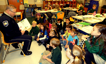 Sheriff's Dep, Eric Eilers reads a book to 4th-graders in the classroom of teacher Tara Sibal at Joseph Davies Elementary School on Nov. 14.