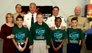 At Joseph Davies Elementary, from left in front row are Principal Donna Schultz, and DA.R.E. essay winners Blake Allemand, Grace Abba, Avani Miller and Quentin Marshall. In back are Sgt. Darrin Miller, Sheriff James Pohlmann, Maj, Chad Clark and Capt. Ronnie Martin.