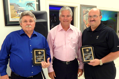 Reserve Division Sgt. Albert Loar, left, and Reserve Division Capt. Joe Ricca, right, with Sheriff James Pohlmann after they were honored for more than 20 years service to the division.
