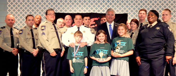 At Our Lady of Prompt Succor School,  D.A.R.E. essay winners were, from left, Trent Jenning, Elizabeth Mahler and Victoria Pohlmann. Immediately behind them are D.A.R.E. instructor Sgt. Darrin Miller, Maj. Chad Clark, Sheriff James Pohlmann and Lt. Lisa Jackson, who heads the D.A.R.E. program. In the back row are officers from the Sheriff's Office Special Investigations Division which includes the Narcotics Unit.