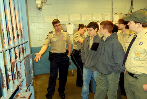 Lt. Justin Meyers of the Sheriff's Office Corrections Division shows a holding cell where prisoners are kept when first brought into the Parish Prison to members of Boy Scout Troop 14 of Chalmette, who toured the facility