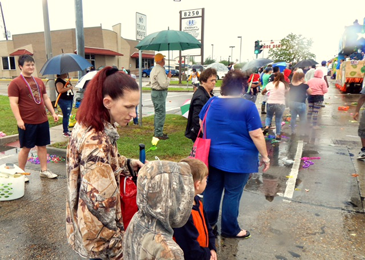 Spectators stand in scattered rain to see the parade.