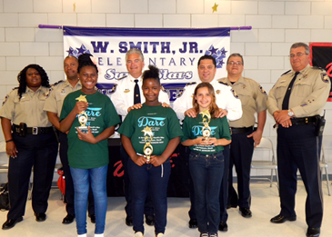 At Wille Smith Jr. Elementary, D.A.R.E. essay contest winners were, in front, Ke-Irell Rhodes, U' Nique McGill and Grace Teal, with in back from left, D.A.R.E. program head Lt. Lisa Jackson, Lt. Richard Jackson, Sheriff James Pohlmann, Maj. Chad Clark,D.A.R.E.instructor Sgt. Darrin Miller, and Lt. Robert Broadhead.