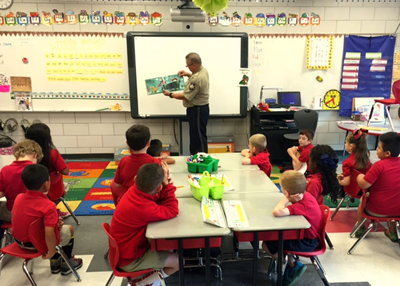 Dep. Sheriff eric Eilers reads to 1st-graders at Lacoste Elementary School in the classroom of teacher Rebekah Topey.