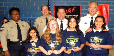D.A.R.E. essay winners at Arabi Elementary were, in front from left, Elena Ozuna, Lilyan Aziz, Avery Edler and Isis Wilcox. In back are Lt. Lisa Jackson, Sgt. Darrin Miller, Maj. Chad Clark and Sheriff James Pohlmann.