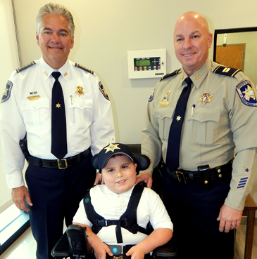 Trever Rickerson, 5, holds a Sheriff's Office badge he was given during a visit Dec. 17 to a station in Arabi. With him are Sheriff James Pohlmann and Capt. Ronnie Martin.