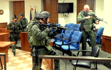 A small courtroom on the first floor is cleared by officers.