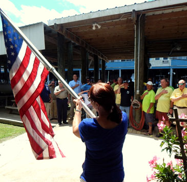 Cindy Broadhead holds an American flag as participants stand and recite The Pledge of Allegiance.