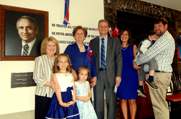 Members of the Rowley family, including, second from left in back, his widow Elizabeth, and son Jack Rowley Jr. next to her,,stand next to the photo and plaque honoring Jack Rowley in the lobby of the Courthouse.
