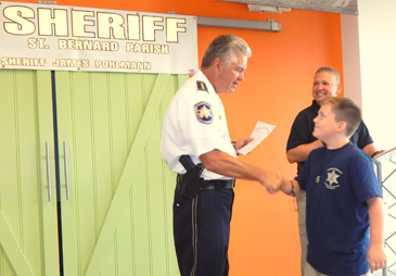 Bob Manual receives his graduation certificate from Sheriff Pohlmann.