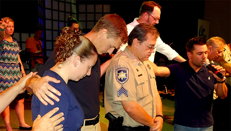 From left, Sheriff's Dep. Amanda Roh, Sheriff's Office Chaplain Aaron Johnson, Sgt. Darren Miller and Celebration Church Assistant Pastor Trevor Truitt take part in a prayer ceremony. In back is Pastor Patrick Eagan.
