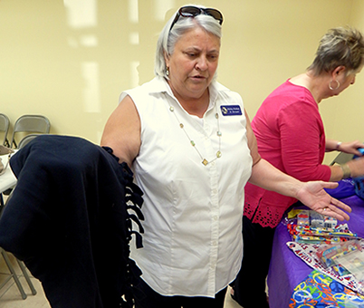 Shirley Pechon holds a blanket, one of the items in a bag for children.. In the background is club member and former Parish Council member Judy Hoffmeister.