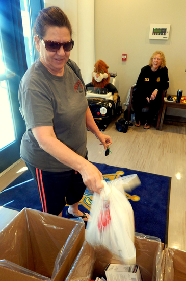 A woman drops off medications during a Drug Take-Back event on Oct. 22 at a Sheriff's Office station in Arabi. In the background is Capt. Pat Childress.