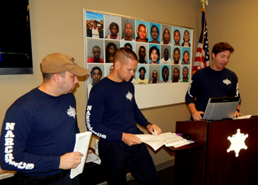 Prior to the round-up of wanted suspects, agents of the SID, from left, Jason Saltalmachia, Lt. Daniel Bostic and Agent Jonathan Smith go over the operation with officers from St. Bernard, State Police, the U.S. Marshal's Fugitive Task Force and the federal Drug Enforcement Administration.
