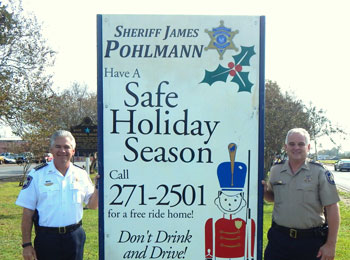 Sheriff James Pohlmann and Capt. Walter Dornan at one of the five signs in the parish announcing the Sheriff's office free Holiday Ride Home program has begun and runs through Jan. 2. The goal is to prevent drinking and driving. Call (504) 271-2501.
