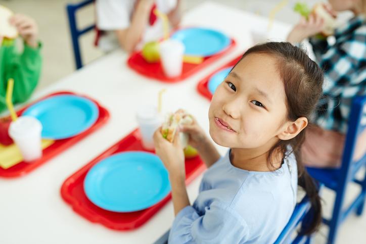 Happy girl eating school lunch