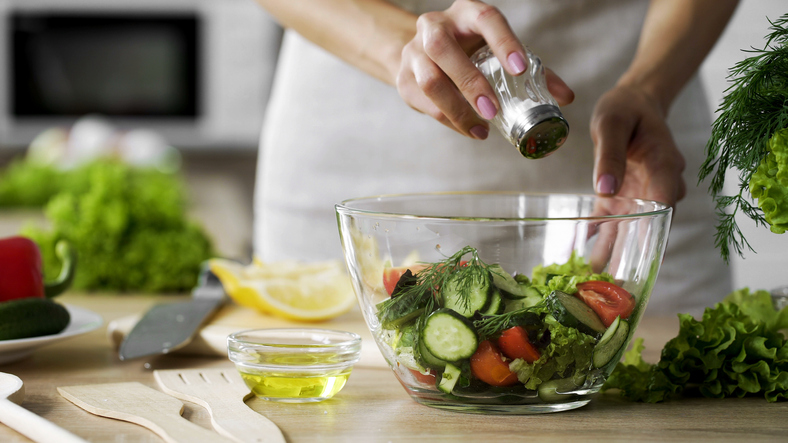 Woman adding salt into a salad bowl