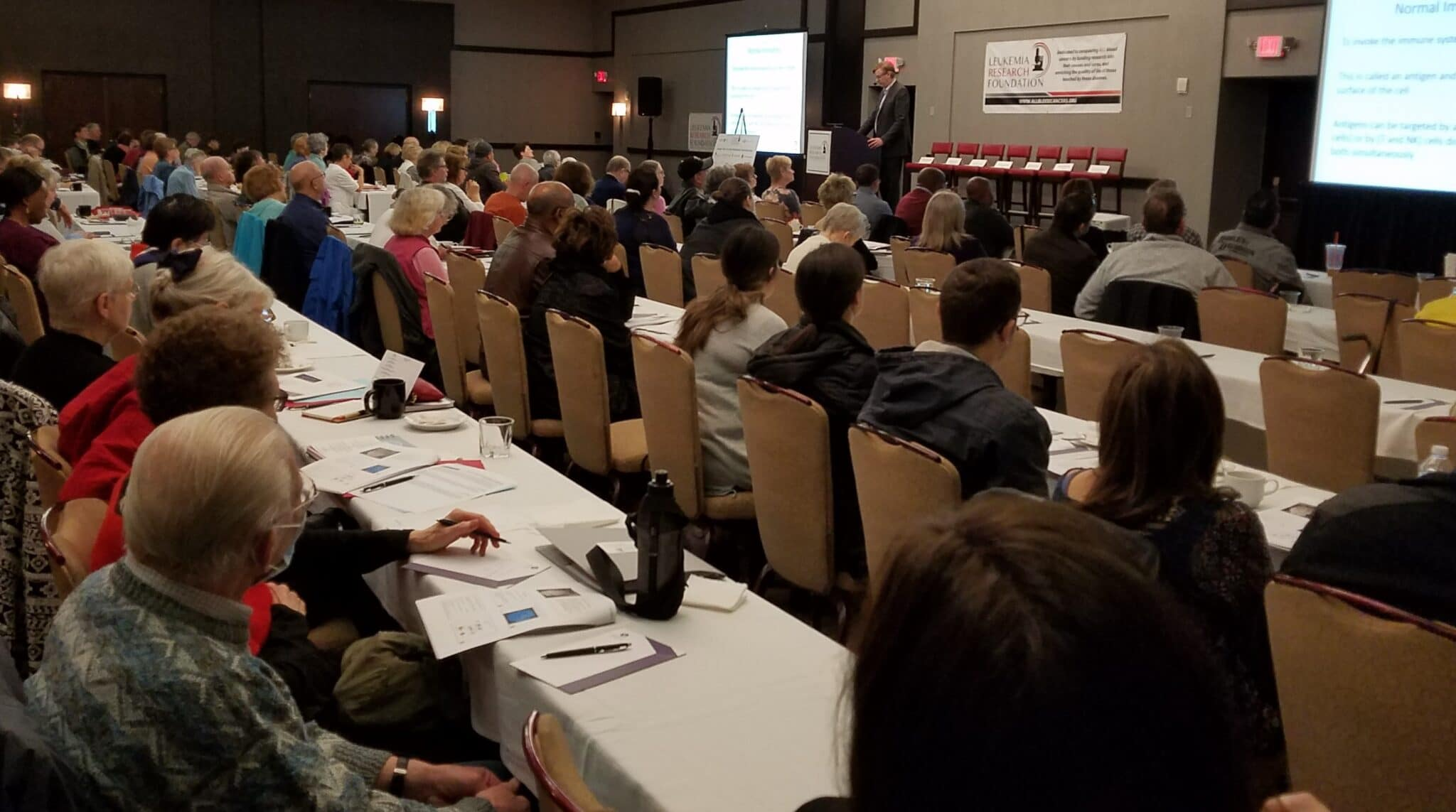 image of large group at Treatment Options for Blood Cancer Patients Conference with presenter