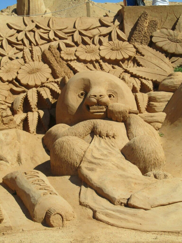 Sand sculpture of a panda with a towel and toothpaste