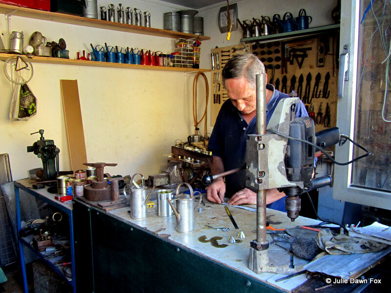 man making tin oil cans in a workshop