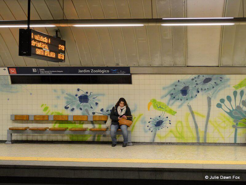 woman waits at Jardim Zoológico metro station with painted tiles by Júlio Resende