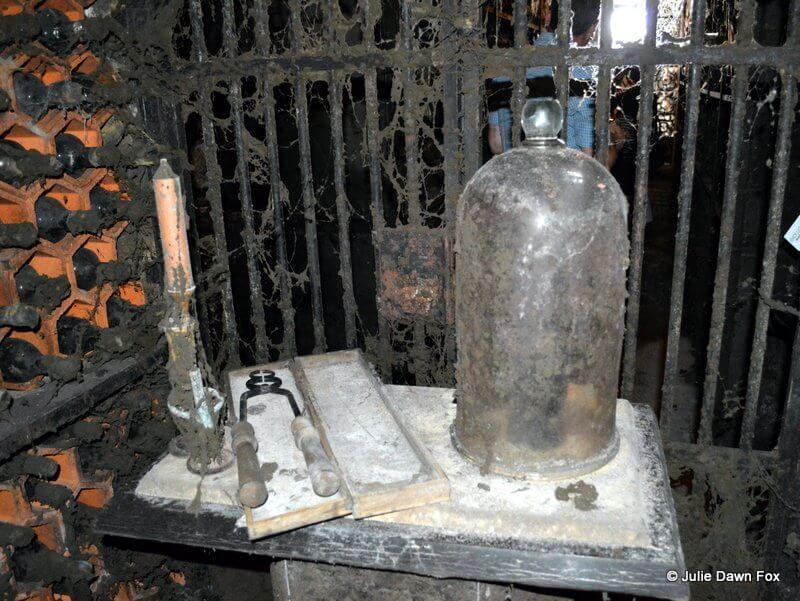 Bottle of 1765 port wine inside a dusty bell jar surrounded by dusty bottles