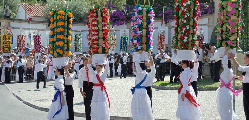 Men help steady the heavy trays, Festa dos Tabuleiros, Tomar, Portugal