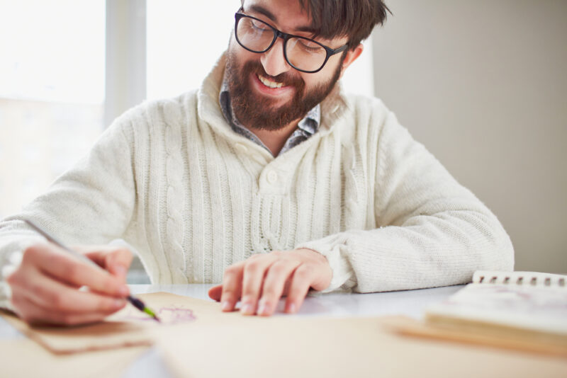 Man with beard and glasses drawing and smiling