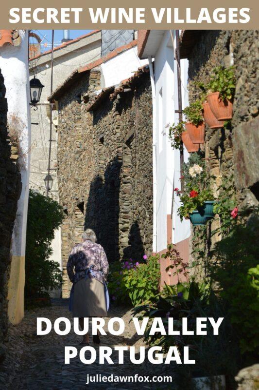 Old lady walking up narrow street. São João da Pesqueira, Douro Valley.