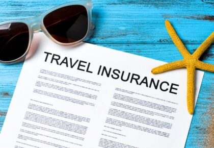 Sunglasses on blue desk. Travel insurance Document