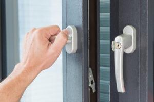 person using lock on home's door