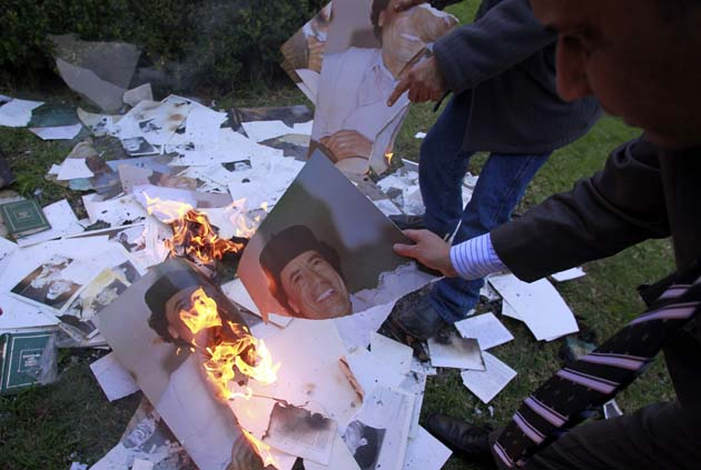 Employees of the Libyan Embassy burn portraits of Gaddafi in Buenos Aires